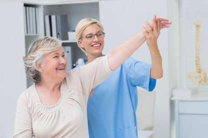 woman helping an elderly woman exercise her arm