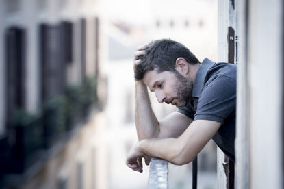 sad man looking out a window