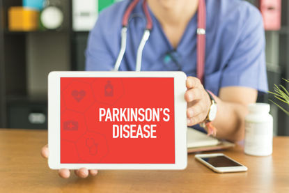 person holding tablet with Parkinson's Disease on it