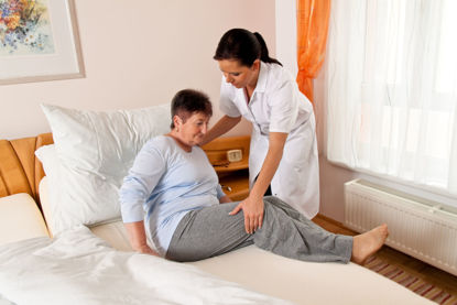 woman helping a person out of bed
