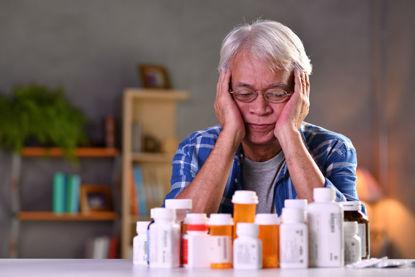man looking at bottles of medication