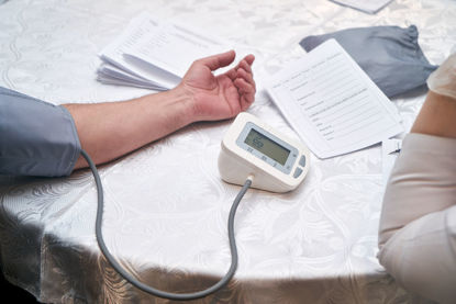 person monitoring another person taking blood pressure