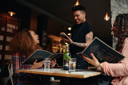 people at a table talking with a server