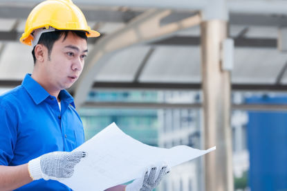 man in hard hat looking at paper