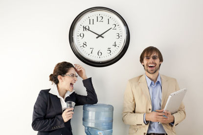 two people laughing around a water cooler