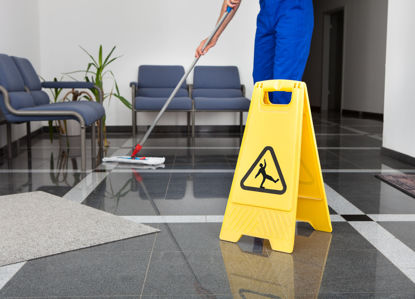 "person mopping floor beside a ""slippery when wet"" placard"