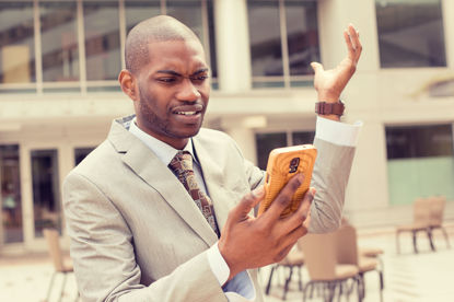 man looking at cellphone and throwing his hand in air