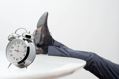 man resting his legs on table with a clock