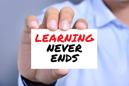 male holding sign stating learning never ends