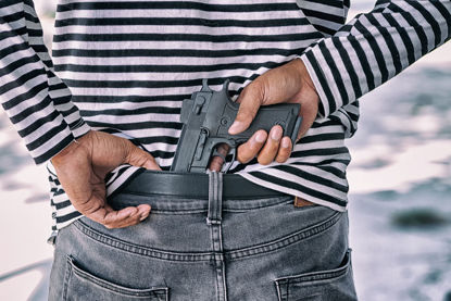 person concealing a gun behind the back