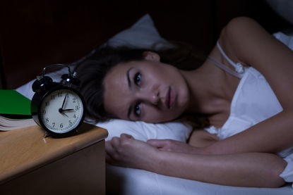 woman lying in bed staring at a clock
