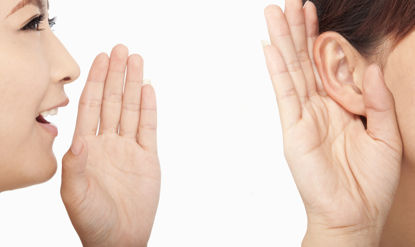 woman talking to a person who has cupped an ear
