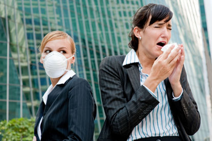 woman wearing a mask standing beside a woman sneezing