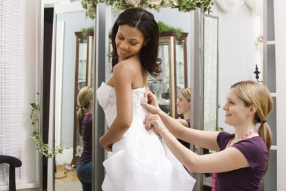 woman helping another woman fit a wedding dress