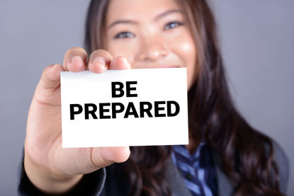 woman holding a be prepared sign