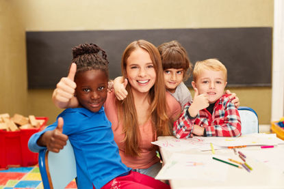 group of children with an adult all giving a thumbs up