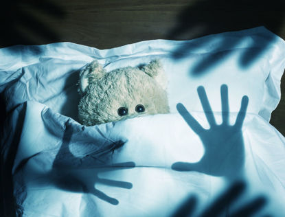 teddy bear under covers hiding from multiple silhouettes of hands