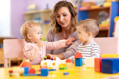 woman observing two children