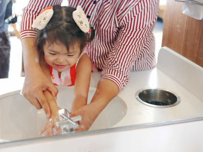 child washing hands with help