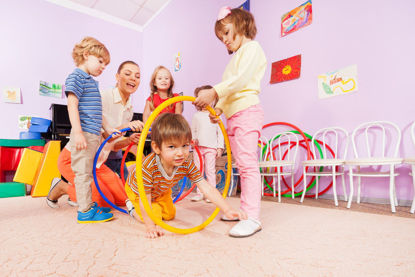 children crawling through hoops during indoor play