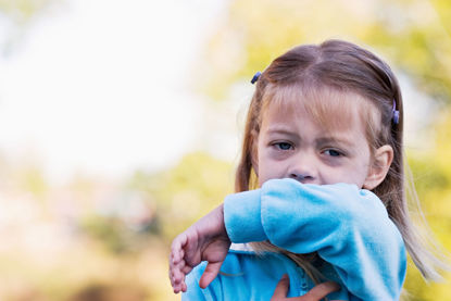 young child coughing into elbow bend
