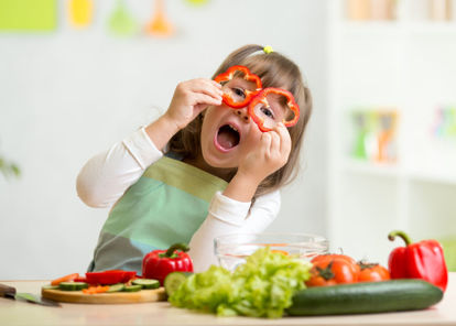 child holding food up to face