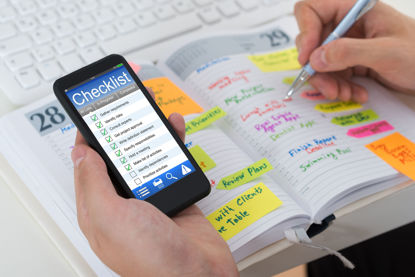 person with smartphone and planner