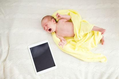 infant beside a tablet