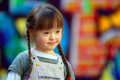 downs syndrome child with playground in background