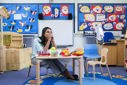 woman sitting at table in early childhood classroom