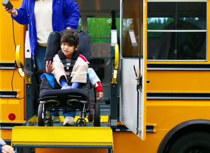 child in a wheelchair on a bus accessibility ramp