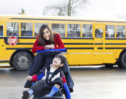 woman with child in wheelchair in front of a bus