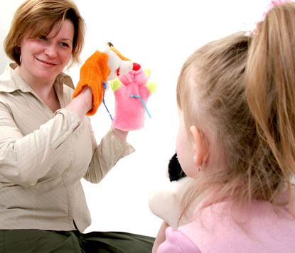 woman using puppets in front of children