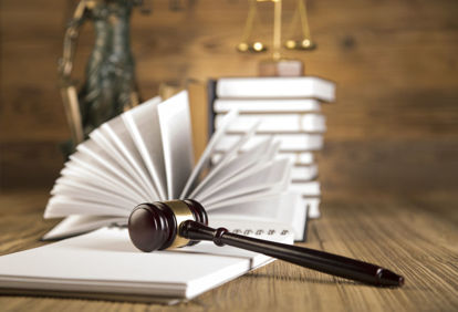 table with open book, gavel, stack of books and lady of justice statue