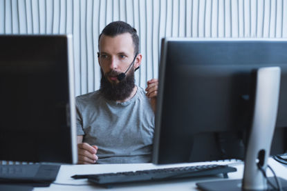 male on headset looking at computer screens