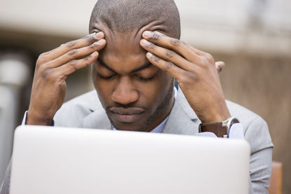 man in front of computer with head in his hands