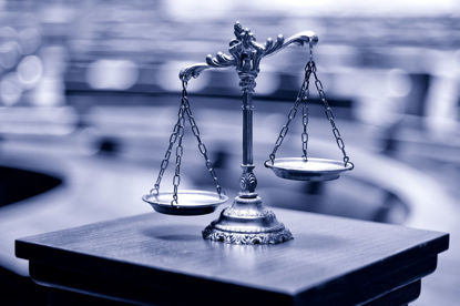 scale on pedestal in front of a blurred courtroom
