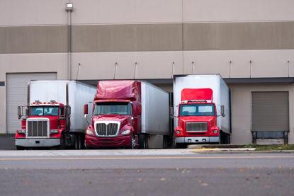 semi trucks backed up to docking bays