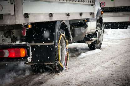 truck with tire chains driving in snow