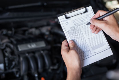 person checking list in front of vehicle engine