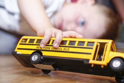child playing with a toy school bus